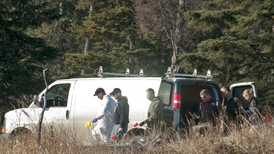 FILE - In this March 22, 2015, file photo, investigators comb the woods after finding the remains of four people who had been missing for nearly 10 months from their home in Kenai, Alaska. An Alaska man shot and killed his girlfriend, her two young daughters and the family dog in 2014 before turning a gun on himself in the woods near the family's home, authorities said Wednesday, June 3, 2015. The determination came a year after the family disappeared in Kenai. (Rashah McChesney/Peninsula Clarion, File)