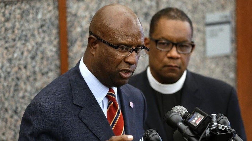 Darnell Williams, head of the Urban League of Eastern Massachusetts, left, speaks with reporters during a news conference as Rev. Mark Scott, of the Azusa Christian Community church, right, looks on, Wednesday, June 3, 2015, at Boston Police Headquarters, in Boston.  Boston police said they have video showing Usaama Rahim, a man who was under 24-hour surveillance by terrorism investigators, lunging with a knife at a police officer and an FBI agent before he was shot and killed.(AP Photo/Steven Senne)