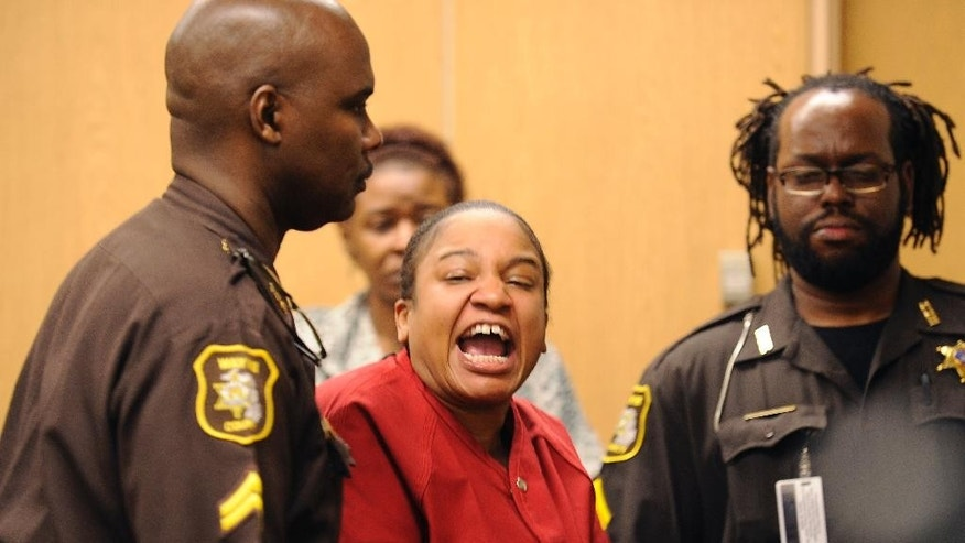 Mitchelle Blair is lead out of the court room by Wayne County Sheriff deputies after an outburst of screaming during a custody hearing before Wayne County Circuit Judge Edward Joseph Thursday, June 4, 2015 in Detroit. Blair was temporarily removed during the custody trial to settle her parental rights to her surviving 8-year-old son and 17-year-old daughter. She was arrested March 24 after court deputies carrying out an eviction at her apartment found the bodies of Stoni Blair, 13, and Stephen Berry, 9, in a deep freezer. Police believe they died months apart in 2012 and 2013.  (Clarence Tabb Jr./Detroit News via AP)  DETROIT FREE PRESS OUT; HUFFINGTON POST OUT