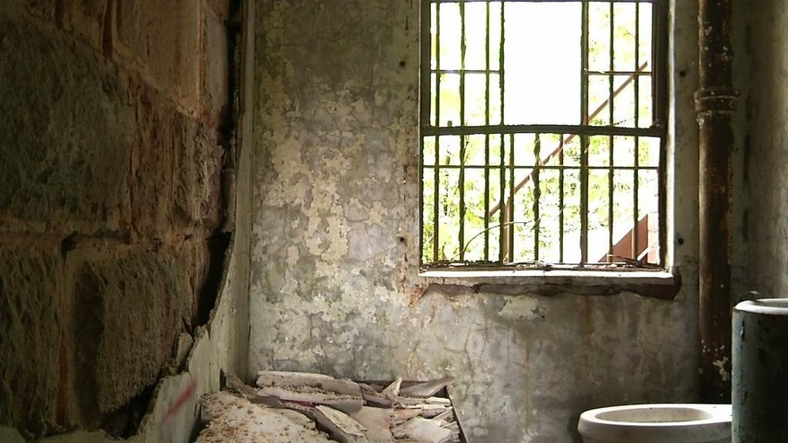 In this June 3, 2015, image taken from video, an underground prison cell is shown at the old Meriwether County jail in Greenville, Ga. The jail, southwest of Atlanta, fell into disrepair after it closed in the mid-1980s. The 119-year-old relic of narrow, aged hallways and small, worn prison cells is being renovated into a home and museum. (AP Photo/Alex Sanz)