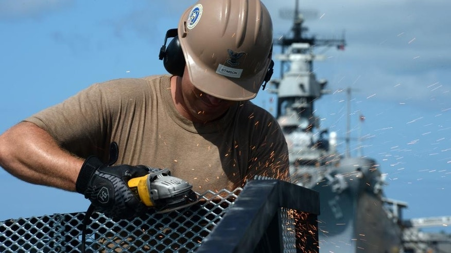 In this Wednesday, June 3, 2015, photo provided by the U.S. Navy, steelworker 2nd Class William Stimson, assigned to Construction Battalion Maintenance Unit 303, grinds metal railings during the repairs of the floating dock next to the USS Arizona Memorial in Pearl Harbor, Hawaii.  Repairs to the damaged dock have been taking longer than expected, which will delay the reopening of the Pearl Harbor landmark at least a day, the navy and National Park Service said Wednesday.  (Mass Communication Specialist 2nd Class Laurie Dexter/U.S. Navy via AP)