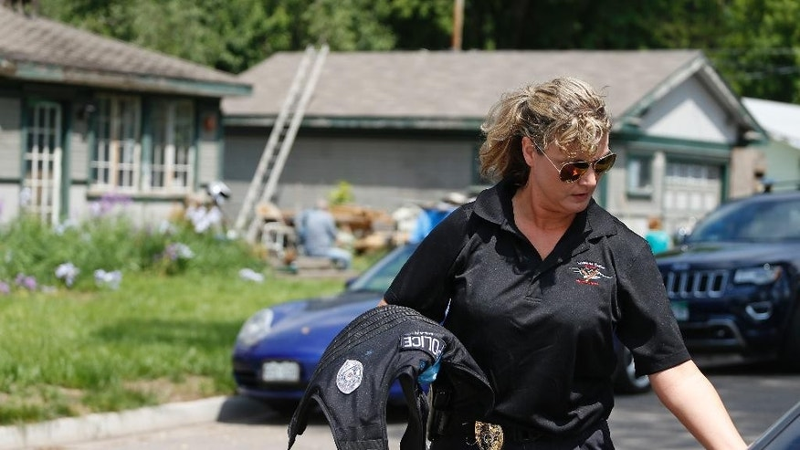 A police officer puts her bulletproof vest into her car after searching for potential clues at the home of a slain man - whose name is yet to be officially released - who was shot and killed the night before, in Loveland, Colo., Thursday, June 4, 2015. The overnight killing of the man on a sidewalk near his home in this in this northern Colorado town has raised alarm that a serial shooter might be trolling the area's roads after a bicyclist was gunned down and a driver was wounded nearby in less than two months. The FBI refuses to comment, but has offered a $10,000 reward for information in the first two shootings, which local police say are related. (AP Photo/Brennan Linsley)