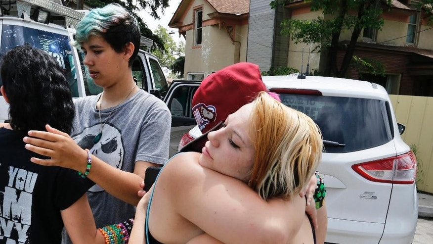 Ciera Rogers, far right, receives condolences from her friend Sam Hinde, on the loss of Rogers' grandfather, who was shot and killed the night before on a sidewalk near his home, in the northern Colorado town of Loveland, Colo., Thursday, June 4, 2015. At left, facing, Emmett Pelissier hugs Ciera Rogers' sister Sadie. The overnight killing in this northern Colorado city has raised alarm that a serial shooter might be trolling the area's roads after a bicyclist was gunned down and a driver was wounded nearby in less than two months.  (AP Photo/Brennan Linsley)