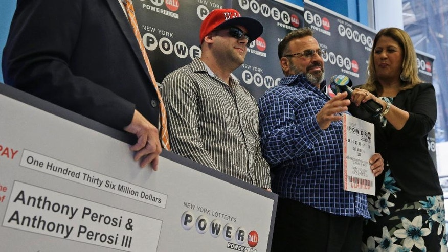 Anthony Perosi, second from right, holding a copy of the winning power ball ticket and his so Anthony Perosi III, second from left, talk to reporters during a ceremony in which New York's Lottery Yolanda Vega, right,  presented an over-sized $136,000,000 prize check to the Staten Island plumber, Thursday, June 4, 2015, in New York.  (AP Photo/Mary Altaffer)