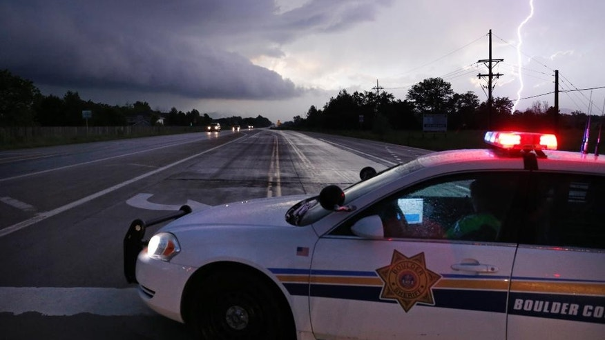 Lighting illuminates the sky over a police  checkpoint at a closed road as a bad storm with tornadoes and hail passes over west of Longmont, Colo., Thursday, June 4, 2015. A tornado that touched down in northern Colorado damaged a handful of homes and brought flooding and marble-sized hail to some areas. (AP Photo/Brennan Linsley)