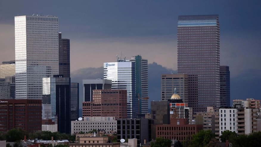 Storms packing tornadoes and hail darken the sky behind the city skyline Thursday, June 4, 2015, in Denver. Severe weather has hit in several locations along Colorado's Front Range during the day, prompting forecasters to issue tornado and flood warnings for the night ahead. (AP Photo/David Zalubowski)