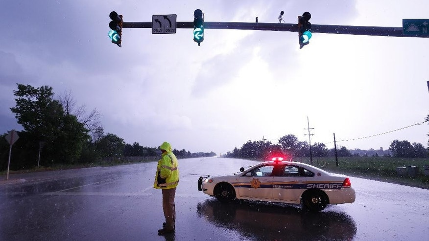 Lightning illuminates the sky over a police checkpoint at a closed road as a bad storm with tornadoes and hail passes over west of Longmont, Colo., Thursday, June 4, 2015. A tornado that touched down in northern Colorado damaged a handful of homes and brought flooding and marble-sized hail to some areas. (AP Photo/Brennan Linsley)