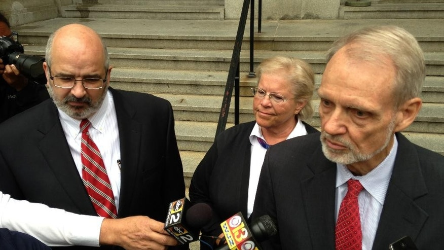 David Irwin, an attorney for former Episcopalian Bishop Heather Cook, center, talks to reporters after her trial was postponed on Thursday, June 4, 2015 in Baltimore. Cook is charged in the drunken-driving death of bicyclist Tom Palermo in December. Attorney Jose Molina, who also is representing Cook, is standing at left.  (AP Photo/Brian Witte)