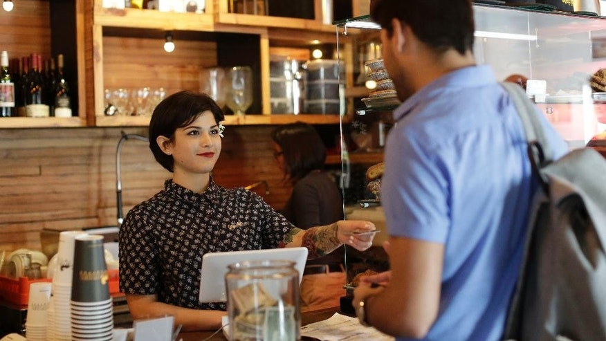In this Thursday, June 4, 2015, photo, Jazmin Donati, left, hands a customer his credit card after making a sale at Panther Coffee, in Miami.  The Federal Reserve releases its April report on consumer borrowing on Friday, June 5, 2015. (AP Photo/Lynne Sladky)
