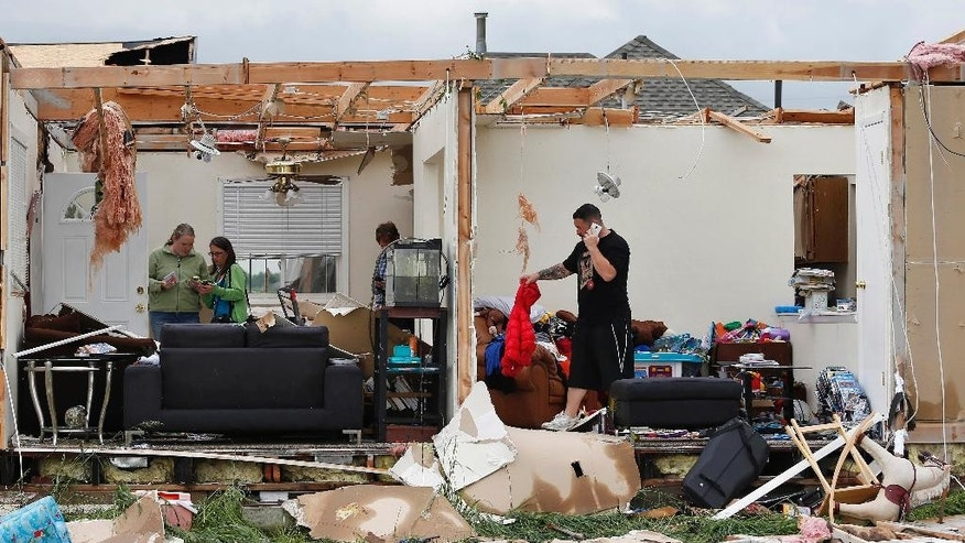 Brandon Scott salvages items from his half-gutted home, where he and family members rode out the previous night's tornado in the basement, southwest of the town of Berthoud, Colo., Friday, June 5, 2015. A storm and a tornado that touched down in northern Colorado Thursday night damaged homes and brought flooding and marble-sized hail to some areas. (AP Photo/Brennan Linsley)