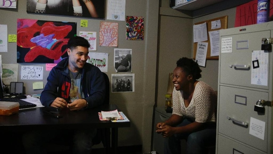 In this Tuesday, April 14, 2015 photo, assistant case manager Shaina Clasberry, right, and Darius Lane laugh together in the office at Beachwood Home in Los Angeles. Lane is a resident at Beachwood House, a group home for foster kids without a home. (AP Photo/Jae C. Hong)