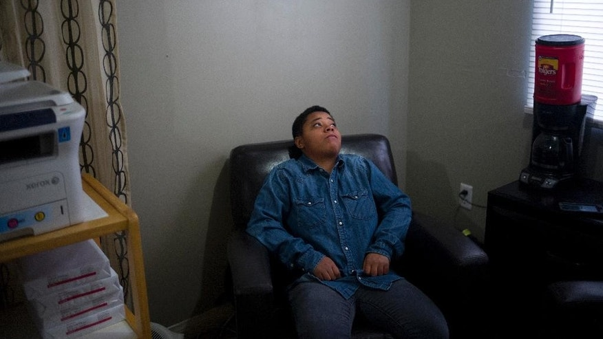 In this Tuesday, March 31, 2015 photo, Angelicah Malone sits in the office at Beachwood House, a group home for foster kids without a home, in Los Angeles. Malone, 17, had never known a stable home. She had grown up living with her mother in hotels. They rarely stayed in one place for more than a month. She doesn't know how many times they moved, but she guesses it was at least 30 or 40. (AP Photo/Jae C. Hong)