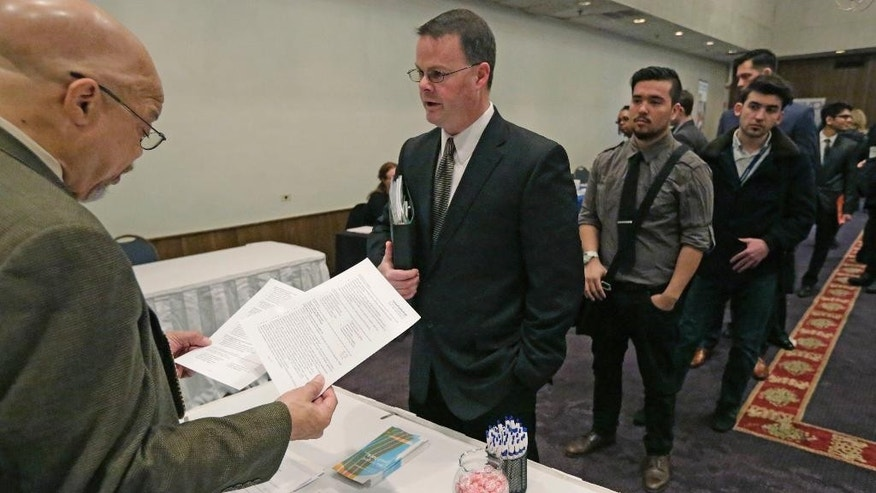 In this April 22, 2015 photo, Ralph Logan, general manager of Microtrain, left, speaks with James Smith who is seeking employment during a National Career Fairs job fair in Chicago. The U.S. economy is churning out a lot of jobs but not a lot of financial security for many of the people who hold them. (AP Photo/M. Spencer Green)