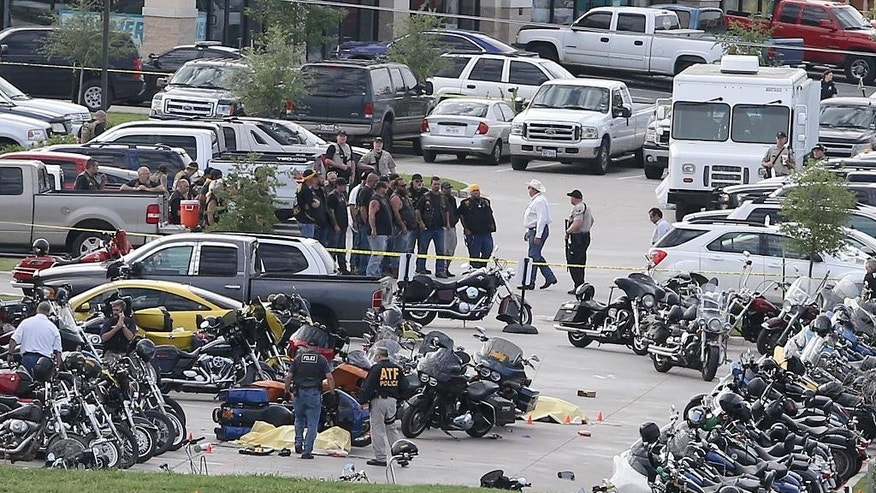 FILE - In this May 17, 2015 file photo, authorities investigate a shooting in the parking lot of the Twin Peaks restaurant, in Waco, Texas. Six witnesses say they heard a few pistol shots before automatic fire took over during a shootout last month at a Waco Twin Peaks restaurant. Police have acknowledged firing on armed bikers, but say they cannot address how many of the nine dead and 18 wounded were shot by bikers and how many were shot by officers. (AP Photo/Jerry Larson, File)