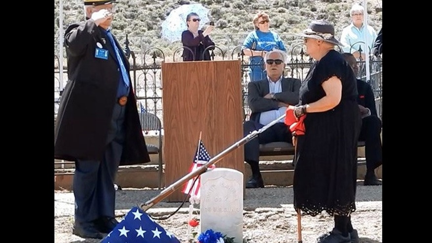 June 7, 2015: John Riggs of the Sons of Union Veterans of the Civil War, left, and Linda Clements of the Historical Society of Dayton Valley pay their respects to Pvt. Scott Carnal of the 1st Kansas Colored Infantry during a ceremony at his grave in Dayton, 30 miles south of Reno, Nev.