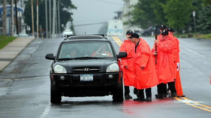 Law enforcement officers check a vehicle at a checkpoint near the Clinton Correctional Facility, background, on Monday, June 8, 2015, in Dannemora, N.Y. Two murderers who escaped from the prison by cutting through steel walls and pipes remain on the loose Monday as authorities investigate how the inmates obtained the power tools used in the breakout. (AP Photo/Mike Groll)