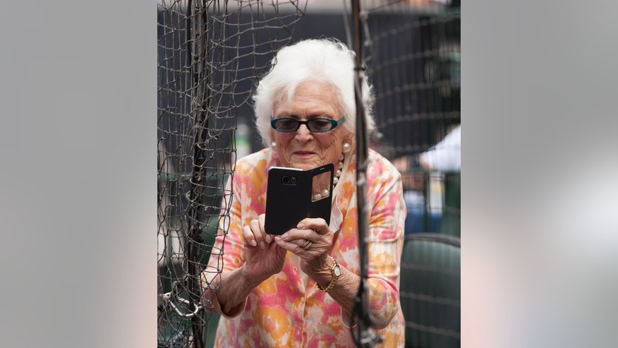 May 3, 2015: In this file photo, former first lady Barbara Bush takes photos with her cell phone before the Seattle Mariners take on the Houston Astros in a baseball game in Houston, Texas.