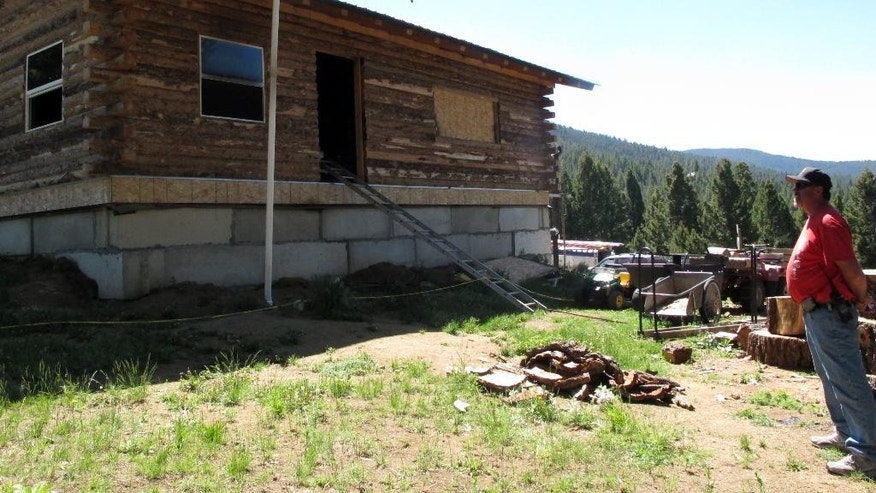 Detective Steve Barclay stands in front of a fire-damaged cabin in the Beaverhead-Deerlodge National Forest outside Deer Lodge, Mont., on Monday, June 8, 2015, where a Montana man shot and killed his wife and three children Sunday morning, set a fire in the family's remote cabin and then killed himself, officials in Anaconda-Deer Lodge County said. Detective Steve Barclay said an investigation determined the man shot his wife and 1-year-old child inside, then went outside and shot two other children — ages 4 and 6. He carried the bodies of the children inside and laid them down on a bed in the cabin, Barclay said. (AP Photo/Matt Volz)