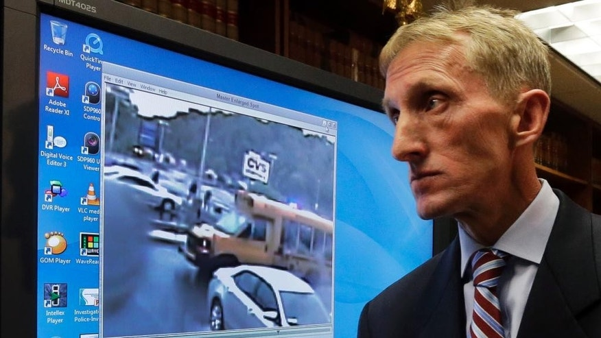 "Commissioner of the Boston Police Department William Evans walks past a monitor after releasing a surveillance video during a press conference Monday, June 8, 2015, in Boston, which police say shows the fatal shooting of a Boston man suspected of plotting to kill police officers. The video comes from a restaurant across the street, and the figures shown are blurry. Police and the FBI say it shows officers shooting 26-year-old Usaama Rahim on June 2 in the city's Roslindale neighborhood after they attempted to question him about ""terrorist-related information."" (AP Photo/Elise Amendola)"