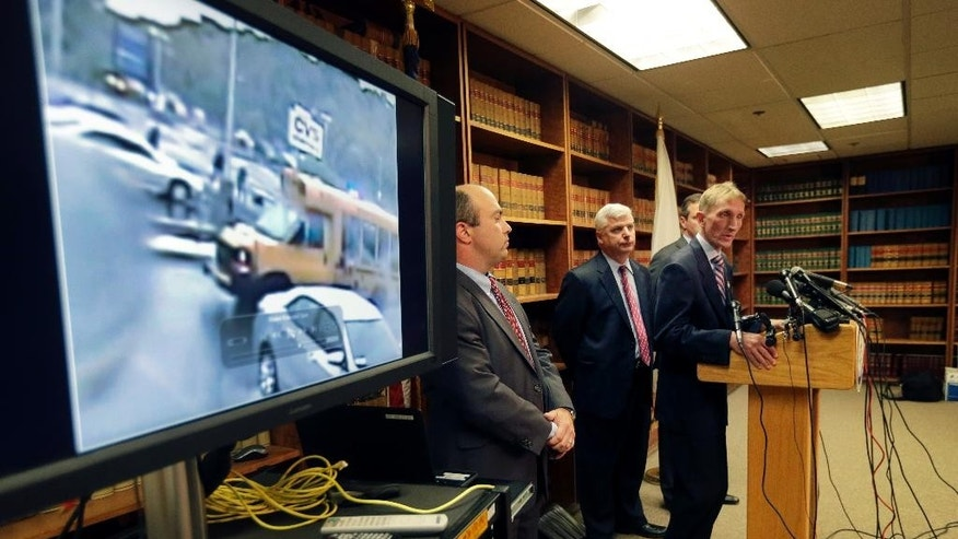 "Commissioner of the Boston Police Department William Evans speaks as First Assistant Suffolk County District Attorney Patrick Haggan, far left, and Suffolk County District Attorney Daniel Conley listen after releasing a surveillance video during a press conference Monday, June 8, 2015, in Boston, which they say shows the fatal shooting of a Boston man suspected of plotting to kill police officers. The video comes from a restaurant across the street, and the figures shown are blurry. Police and the FBI say it shows officers shooting 26-year-old Usaama Rahim on June 2 in the city's Roslindale neighborhood after they attempted to question him about ""terrorist-related information."" (AP Photo/Elise Amendola)"