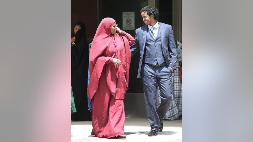 Mohamed Ali Omar, right, is greeted outside the federal courthouse, Tuesday, June 9, 2015, in Minneapolis. Omar, convicted of threatening FBI agents who were conducting a terror investigation, was released from custody Tuesday and his sentencing was postponed as a federal judge weighs whether a recent U.S. Supreme Court decision will affect the case. (Elizabeth Flores/Star Tribune via AP)