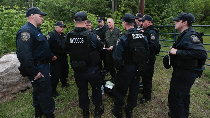 State forest ranger Dan Fox reviews a map with members of the New York State Department of Corrections and Community Supervision emergency response team before entering a wooded area in search of two prisoners who escaped from the Clinton Correctional Facility on Monday, June 8, 2015, in Dannemora, N.Y. The two murderers who escaped from the prison by cutting through steel walls and pipes remain on the loose Monday as authorities investigate how the inmates obtained the power tools used in the breakout. (AP Photo/Mike Groll)