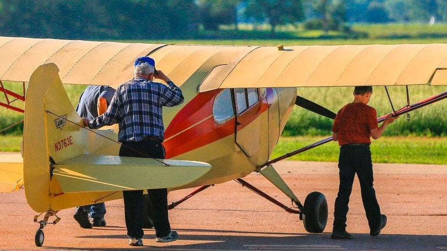 In this June 1, 2015 photo, Gene Martin, owner of Martin Field, center, helps instructor Scott Currie, left, and 12-year-old flight student Pierce Turner, right, push an Aeronca Chief aircraft from it's parking spot onto the runway, in South Sioux City, Neb. Martin recalls when teenagers would bike out to the airfield and pay for flight lessons with the money they earned from paper routes. Now, young people seem more interested in video games or driving cars, Martin said. The number of flight instructors at his field as fallen from 12 to 3, and they're not especially busy. (AP Photo/Nati Harnik)