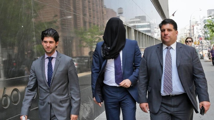 FILE - In this May 19, 2015 file photo, Wojciech Braszczok, center, is led into court with his face covered in New York. The undercover New York Police Department detective and a co-defendant were acquitted Tuesday, June 9, 2015 of the most serious charges but convicted of lesser crimes for participating in a September, 2013 motorcycle rally that devolved into highway pandemonium as an SUV driver was pulled from his window and beaten bloody in front of his wife and toddler. (AP Photo/Mary Altaffer, File)
