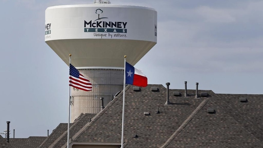 In this June 8, 2015 photo, a water tower with a city slogan painted across it is seen behind a housing area in McKinney, Texas. McKinney is an affluent Dallas suburb that is among the nation's fastest-growing cities, with highly regarded public schools and nationally recognized livability rankings. But a video showing a white police officer wrestling a black girl to the ground at a neighborhood pool party has renewed racial tensions in a city that only three years ago settled litigation alleging public housing segregation. (AP Photo/Ron Jenkins)