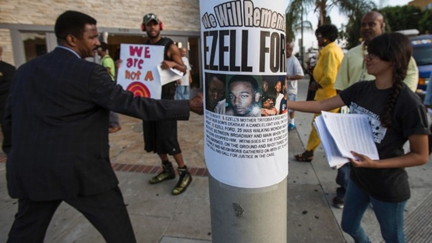 FILE - In this Aug. 19, 2014, file photo, a poster reads 'We Will Remember Ezell Ford' in front of Paradise Baptist Church before a community forum in Los Angeles, to discuss the Aug. 11 police shooting of Ezell Ford. (AP Photo/Ringo H.W. Chiu, File)