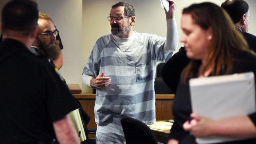 Frazier Glenn Miller Jr., also know as Frazier Glenn Cross Jr. holds up copies of his motion for acquittal to give to members of the media during a hearing  Wednesday, June 10, 2015 in Olathe, Kan.  Miller Jr., 74,  is accused of killing three people on April 13, 2014 at two Jewish sites in the Kansas City suburb of Overland Park, Kansas.  (Shane Keyser/The Kansas City Star via AP)