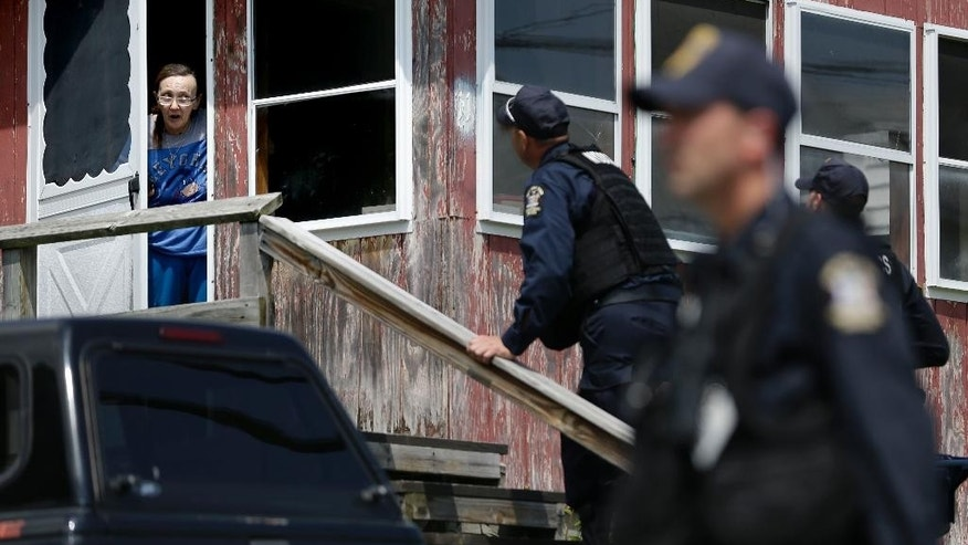 Law enforcement officers question a woman, Wednesday, June 10, 2015, who lives near the prison in Dannemora, N.Y., as they searched houses near the maximum-security prison in northern New York where two killers escaped using power tools. State Police said the fifth day of searching will entail going from house to house in Dannemora, where David Sweat and Richard Matt cut their way out of the Clinton Correctional Facility.  (AP Photo/Seth Wenig)