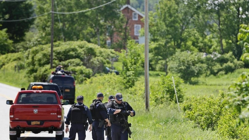 Law enforcement officers walk the streets in Dannemora, N.Y., as they searched houses near the maximum-security prison in northern New York where two killers escaped using power tools,Wednesday, June 10, 2015.  State Police said the fifth day of searching will entail going from house to house in Dannemora, where David Sweat and Richard Matt cut their way out of the Clinton Correctional Facility.  (AP Photo/Seth Wenig)