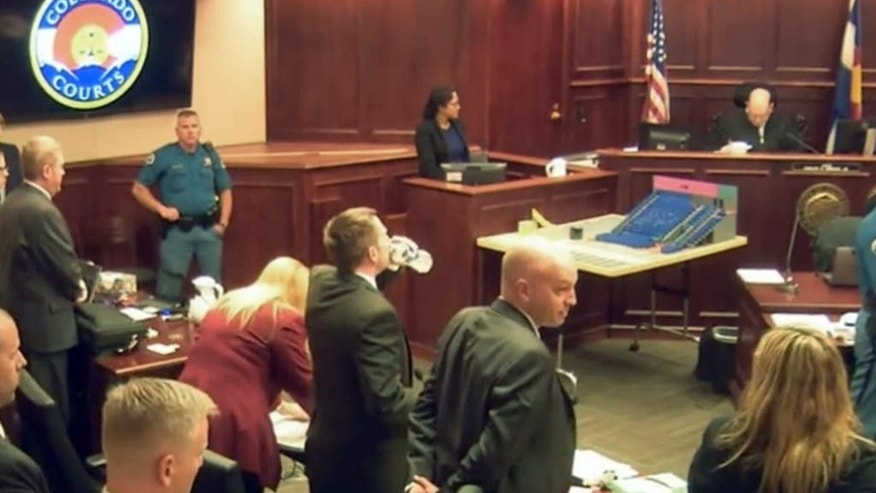 In this image made from a video, the courtroom stands as the jury is excused following Gargi Datta's testimony in a trial for Colorado theater shooter James Holmes, Wednesday, June 10, 2015, in Centennial, Colo. Datta, a former girlfriend of Holmes, said Wednesday that she met Holmes in 2011 and that they went to a horror film festival on their first date. Holmes pleaded not guilty by reason of insanity in the July 2012 shooting at a suburban Denver movie theater that killed 12 people and injured 70. (Colorado Judicial Department via AP, Pool)