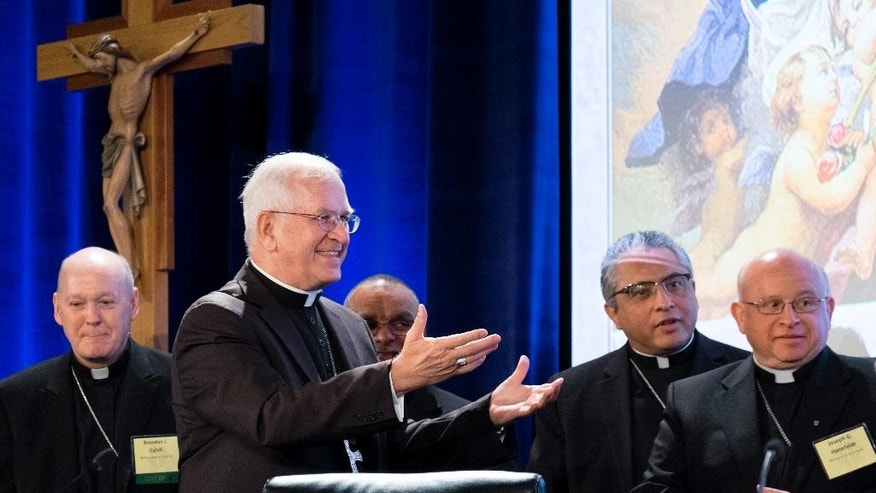 Archbishop Joseph Kurtz, right, of Louisville, and president of the U.S. Conference of Catholic Bishops, greets new members of the U.S. Conference of Catholic Bishops' during the Spring General Assembly in St. Louis, Wednesday, June 10, 2015. Roman Catholic bishops are condemning racism in the U.S. in light of national tensions over police treatment of African-Americans. (AP Photo/Sid Hastings)