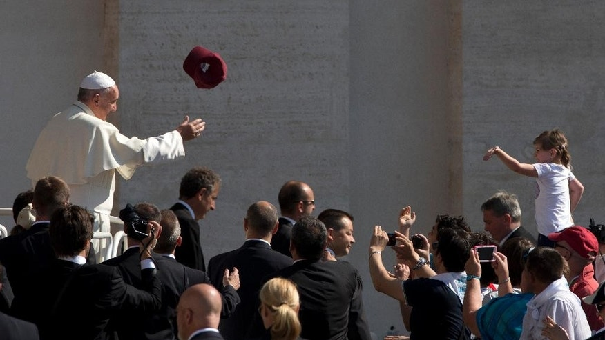 A worshipper tosses a hat into the air as Pope Francis arrives for his weekly general audience in St. Peter's Square, at the Vatican, Wednesday, June 10, 2015. (AP Photo/Alessandra Tarantino)