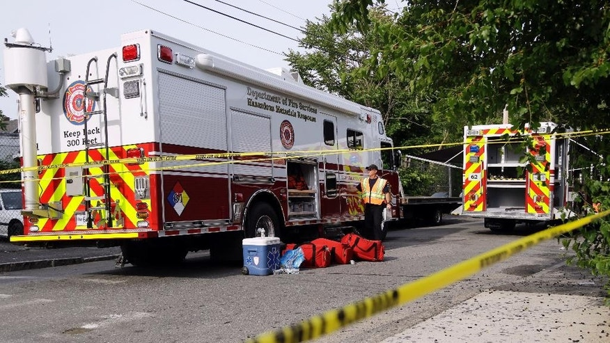 An emergency responder works at the scene of a home in Lowell, Mass., Thursday, June 11, 2015, where authorities say a man who was apparently distraught over a failing relationship released chemical gases killing himself and sending 11 other people to the hospital. (AP Photo/Elise Amendola)