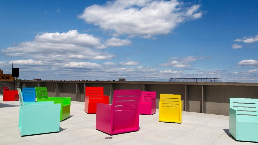 FILE - In this April 21, 2015 file photo, painted chairs by Mary Heilmann appear on a terrace at the Whitney Museum of American Art in New York. New York has opened a number of major new attractions lately, including the Whitney Museum and One World Trade Center observatory, but classics like the Brooklyn Bridge and Times Square are also always at the top of visitors' lists. (AP Photo/Mark Lennihan, File)