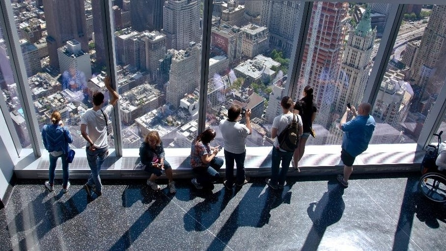 FILE - In this May 29, 2015 file photo, visitors to the One World Observatory view the city and beyond from the 101st floor in New York.  The World Trade Center observatory gives visitors a view of the city and its surroundings from above 1,250 feet, with sight lines stretching 50 miles past the Manhattan skyline. (AP Photo/Bebeto Matthews, File)