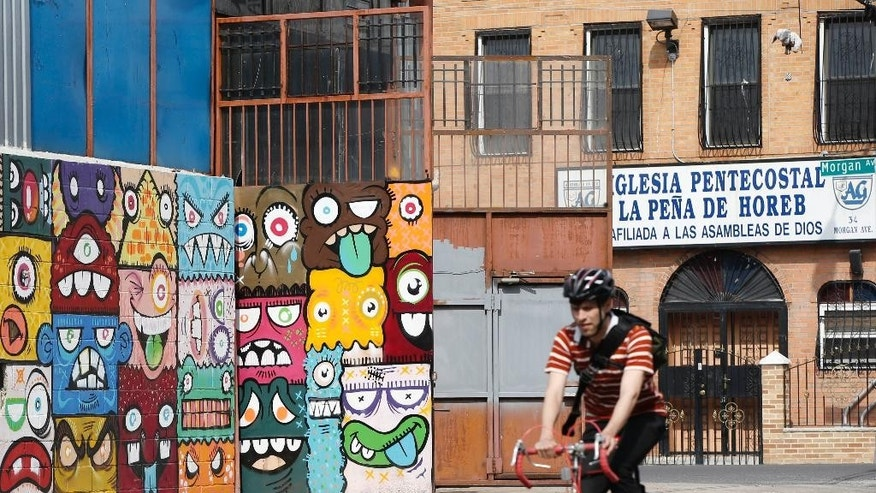 FILE - In this April 22, 2014 file photo, a cyclist pedals by a a street art mural and a storefront church, in Brooklyn's Bushwick neighborhood in New York. The neighborhood, once considered dangerous, is beginning to attract tourists and hipsters. (AP Photo/Kathy Willens, File)