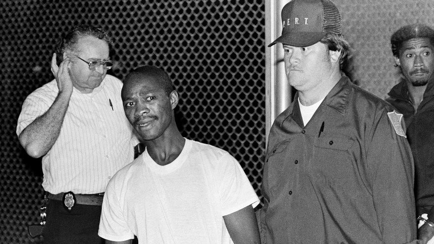 FILE - In this June 2, 1984 file photo, Derrick Lynn Peterson, second from left, and Earl Clanton Jr., far right, are escorted from the Warren County jail to a waiting van in Warrenton, N.C. after they were recaptured following their prison break. Peterson and Clanton escaped with four other death row inmates from the Meckeinberg Correctional Center in Boydton, Va., the previous day. As the hunt for two escaped killers in New York stretches to almost a week, a review of past high-profile escapes shows most do in fact get caught sooner or later, tripped up by any number of missteps or miscalculations. (AP Photo/Steve Helber, File)