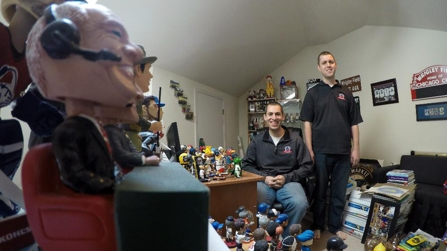 In this April 16, 2015,  photo, Phil Sklar, seated, and Brad Novak sit with some of the bobbleheads they have collected since quitting their jobs last year to start the National Bobblehead Hall of Fame and Museum in downtown Milwaukee. They've already collected 4,000 bobbleheads of sports players, mascots, characters, regular and famous people and hope to have 10,000 by the time they open next year. (AP Photo/Carrie Antlfinger)