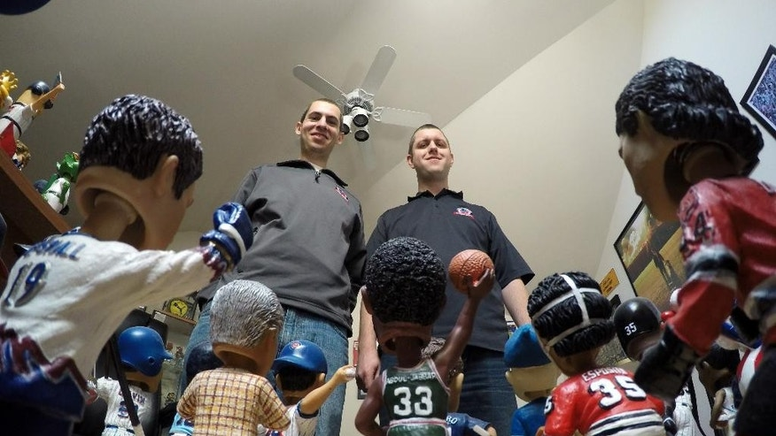 In this April 16, 2015, photo, Phil Sklar, left, and Brad Novak sit with some of the bobbleheads they have collected since quitting their jobs last year to start the National Bobblehead Hall of Fame and Museum in downtown Milwaukee. They've already collected 4,000 bobbleheads of sports players, mascots, characters, regular and famous people and hope to have 10,000 by the time they open next year. (AP Photo/Carrie Antlfinger)