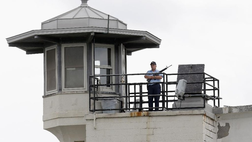 A prison employee stands guard on a tower at the Clinton Correctional Facility in Dannemora, N.Y., Wednesday, June 10, 2015. Police were resuming house-to-house searches near the maximum-security prison in northern New York where two killers escaped using power tools, authorities said Wednesday as they renewed their plea for help from the public. (AP Photo/Seth Wenig)