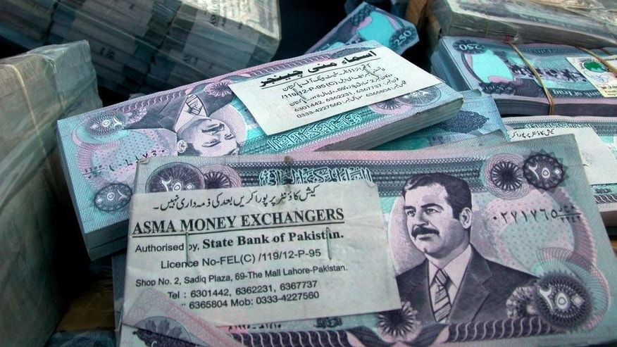 "FILE- In this Dec. 8, 2003 file photo, stacks of old Iraqi dinars portraying ousted leader Saddam Hussein lay in the port of Basra, Iraq. Federal authorities want to seize airplanes, homes, luxury cars and beach properties from a Georgia-based corporation dealing in Iraqi currency. In a federal complaint, prosecutors say Atlanta-based Sterling Currency Group LLC is among the largest sellers of the Iraqi dinar in the U.S. Prosecutors say the business is built on what they describe as a scam to defraud investors hoping to cash in on a ""revaluation"" of the currency. (AP Photo/Nabil Aljurani, File)"