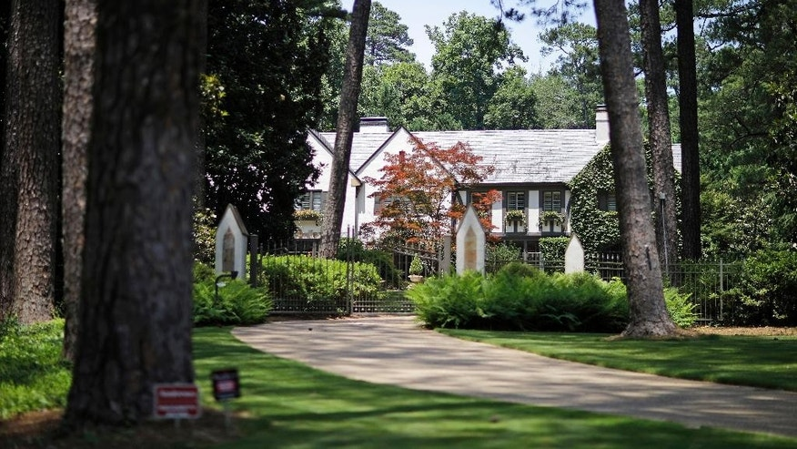 "A mansion listed as an asset to Sterling Currency Group LLC and associated companies stands at 225 Valley Rd NW, Thursday, June 11, 2015, in Atlanta. Federal authorities want to seize the mansion along with airplanes, luxury cars and beach properties from the Georgia-based corporation dealing in Iraqi currency. In a federal complaint, prosecutors say Atlanta-based Sterling Currency Group LLC is among the largest sellers of the Iraqi dinar in the U.S. Prosecutors say the business is built on what they describe as a scam to defraud investors hoping to cash in on a ""revaluation"" of the currency. (AP Photo/David Goldman)"