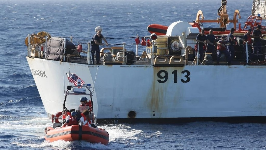 In this photo taken in the Florida Straits on May 17, 2015, members of the U.S. Coast Guard Cutter Charles David Jr, foreground, leaving the USCG cutter Mohawk with six Cuban migrants. U.S. authorities have captured or intercepted more than 2,500 Cuban migrants attempting the risky sea crossing from Cuba to the U.S. since Oct. 1, 2014. (AP Photo/Tony Winton)