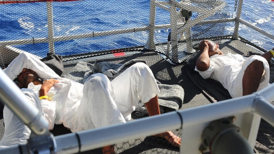 This photo taken in the Florida Straits on May 17, 2015, shows Cuban migrants aboard the U.S. Coast Guard Cutter Charles David Jr. The migrants are given a white jumper, a mat, pillows and blankets and are housed on the deck of the cutter. The U.S. Coast Guard returns any Cuban migrants caught at sea to the communist island.  (AP Photo/Tony Winton)