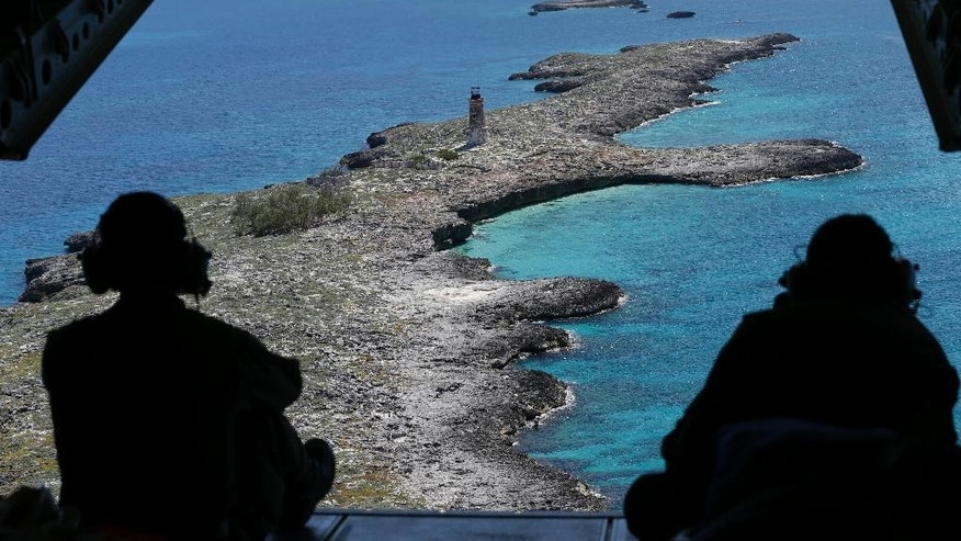 In this, Tuesday, May 19, 2015, photo, U.S. Coast Guard AET-3, Andre McCormick, left, and AMT-2, Julio Guillermo sit on the open ramp at the rear of an HC-144A Ocean Sentry aircraft as they fly over an abandoned lighthouse on Cay Sal Bank in the Bahamas. Despite a historic shift in the relationship between the governments on either side of the Florida Straits, the U.S. Coast Guard still plays a deadly hide-and-seek with Cuban migrants on the high seas, returning to the communist island anyone they catch. Coast Guard pilots routinely fly over remote islands that bookend the Florida Straits, the outcropping of rocks at Cay Sal and the Dry Tortugas and Marquesas west of Key West. (AP Photo/Wilfredo Lee)