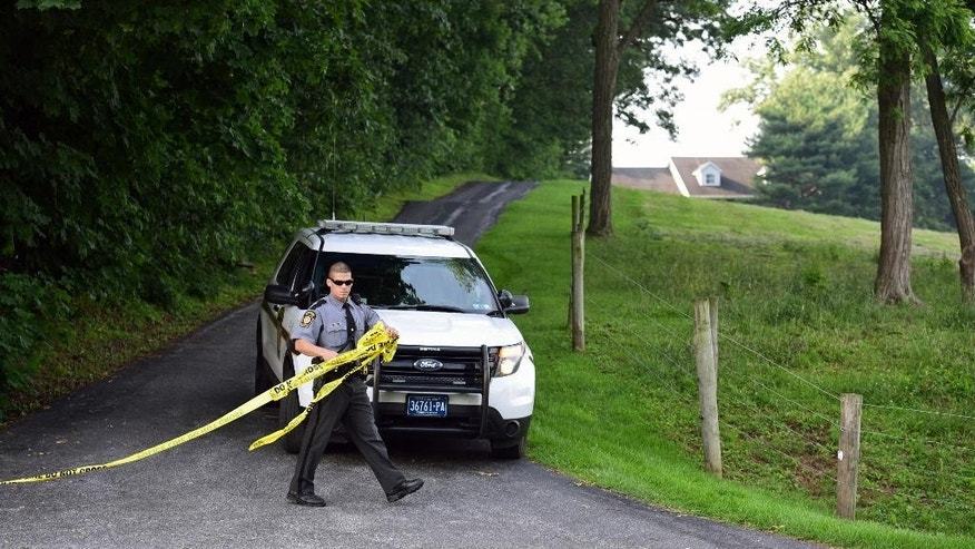 A Pennsylvania state trooper tapes off a driveway at a residence on Spring Valley Road in Quarryville, Pa.(Casey Kreider/LNP via AP)